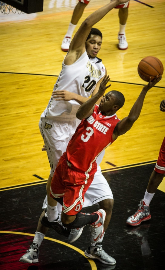 Shannon Scott works to get a shot off over A.J. Hammons